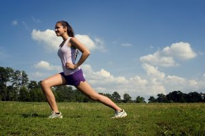 young-woman-stretching-outdoors-before-exercising